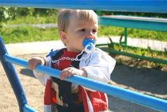 El niño en un patio de los niños Foto de archivo libre de regalías