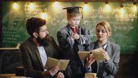 El niño enseña a la mujer y al hombre en escuela Niño en capa del traje y casquillo grandes de la graduación así como la familia  almacen de video