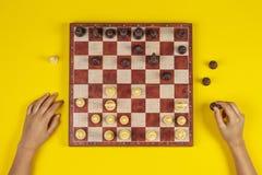 El niño entrega un tablero de ajedrez que juega al juego de ajedrez en el fondo amarillo, visión superior imagen de archivo