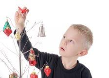 El niño es concentración sobre el adornamiento del árbol de navidad del alambre de metal, con los ornamentos de cristal Imagenes de archivo