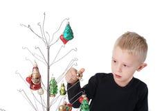 El niño es concentración sobre el adornamiento del árbol de navidad del alambre de metal, con los ornamentos de cristal Fotos de archivo
