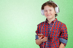 El niño es música que escucha con los auriculares fotografía de archivo libre de regalías