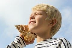 El niño escucha la concha marina Foto de archivo