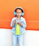 El niño escucha la música en auriculares y smartphone con Foto de archivo libre de regalías