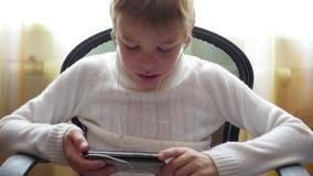 El niño escucha la música en smartphone en los auriculares y los saltos dirigen en hogar almacen de metraje de vídeo