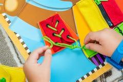 El niño está aprendiendo atar los cordones Fotos de archivo libres de regalías