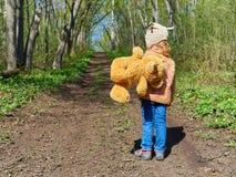 El niño está caminando abajo de la trayectoria con Teddy Bear Imagen de archivo libre de regalías