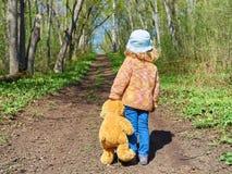 El niño está caminando abajo de la trayectoria con Teddy Bear Imagenes de archivo