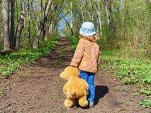 El niño está caminando abajo de la trayectoria con Teddy Bear Imagen de archivo