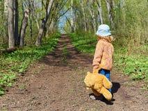 El niño está caminando abajo de la trayectoria con Teddy Bear Foto de archivo libre de regalías