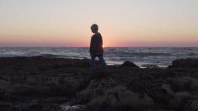 El niño está caminando a lo largo de una playa rocosa metrajes