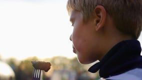 El niño está comiendo la barbacoa en el aire fresco primer almacen de metraje de vídeo