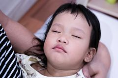 El niño está durmiendo en su protección de la mano del ` s de la mamá Fotografía de archivo