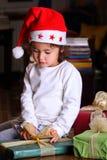 El niño está estudiando sus regalos de la Navidad Foto de archivo libre de regalías