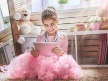El niño está jugando con la tableta imagen de archivo
