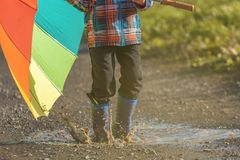 El niño está jugando con el paraguas colorido en un charco imagen de archivo