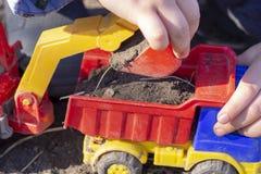 El niño está jugando en la calle con la arena; él carga la tierra en un juguete del camión volquete fotos de archivo