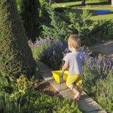 El niño está llevando un carro de jardín del juguete en una casa de campo Fotografía de archivo libre de regalías