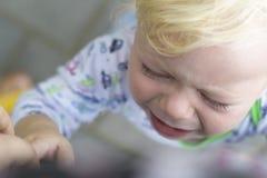 El niño está llorando de la frustración, del dolor o de un mún humor Foto de archivo libre de regalías