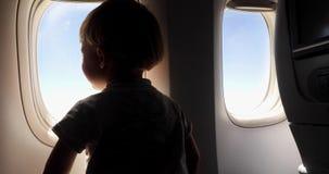 El niño está mirando de la ventana de la porta para el vuelo de los aviones metrajes