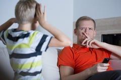 El niño está molestando a su padre imagen de archivo