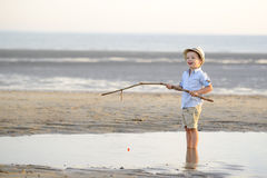 El niño está pescando en la playa en la playa fotos de archivo libres de regalías