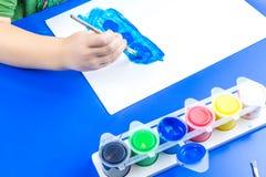 El niño está pintando una imagen con las pinturas de la témpera Imágenes de archivo libres de regalías