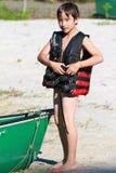 El niño está poniendo en un la más lifevest Fotos de archivo