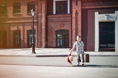El niño está sosteniendo la maleta y el juguete del oso de peluche que cruzan la calle soleada Fotos de archivo