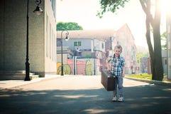 El niño está sosteniendo la maleta y está caminando abajo del s soleado Foto de archivo libre de regalías