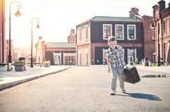 El niño está sosteniendo la maleta y está caminando abajo del s soleado Imagen de archivo libre de regalías
