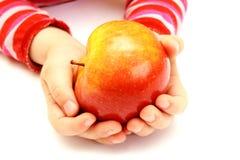 El niño está sosteniendo la manzana fresca Fotos de archivo libres de regalías