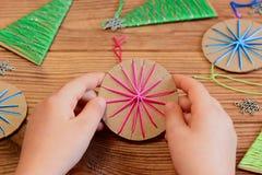 El niño está sosteniendo una bola de la Navidad en sus manos El niño está mostrando una bola de la Navidad Artes y actividades re Fotografía de archivo