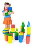 El niño feliz construye un castillo fuera de bloques foto de archivo