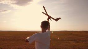 El niño feliz corre con un aeroplano del juguete en un fondo de la puesta del sol sobre un campo El concepto de una familia feliz almacen de metraje de vídeo