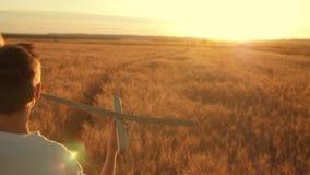El niño feliz corre con un aeroplano del juguete en un fondo de la puesta del sol sobre un campo El concepto de una familia feliz almacen de video