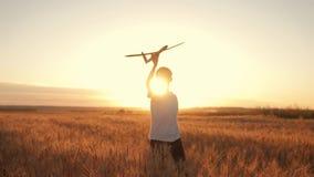 El niño feliz corre con un aeroplano del juguete en un fondo de la puesta del sol sobre un campo El concepto de una familia feliz metrajes