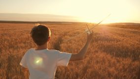El niño feliz corre con un aeroplano del juguete en un fondo de la puesta del sol sobre un campo El concepto de una familia feliz