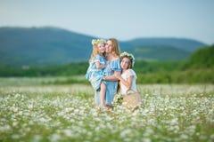 El niño feliz de la madre y de la hija así como las flores amarillas del diente de león en día de verano disfruta del tiempo libr fotos de archivo