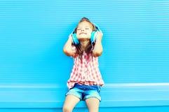 El niño feliz de la niña escucha la música en auriculares Imágenes de archivo libres de regalías