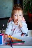 El niño feliz del bebé dibuja con los creyones coloreados de los lápices Fotografía de archivo
