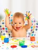El niño feliz dibuja con las manos coloreadas de las pinturas Imagen de archivo