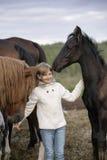 El niño feliz divertido en un suéter blanco y los vaqueros que se colocan entre caballos pare en la sonrisa de la granja Retrato  Foto de archivo