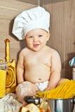 El niño feliz el cocinero del cocinero cocina la comida Imágenes de archivo libres de regalías