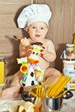 El niño feliz el cocinero del cocinero cocina la comida Imagen de archivo libre de regalías