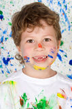 El niño feliz en el suyo pintura-manchó Foto de archivo