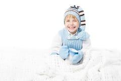 El niño feliz en invierno caliente arropa la taza de la explotación agrícola Imagen de archivo libre de regalías