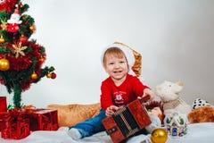 El niño feliz en Santa Bell se sienta debajo del árbol de navidad fotografía de archivo