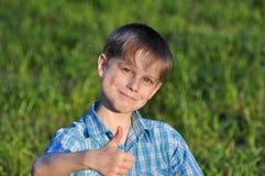 El niño feliz en una hierba verde Imagen de archivo libre de regalías