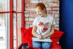 El niño feliz es un adolescente que se sienta en un travesaño y un dibujo de la ventana Fotografía de archivo libre de regalías
